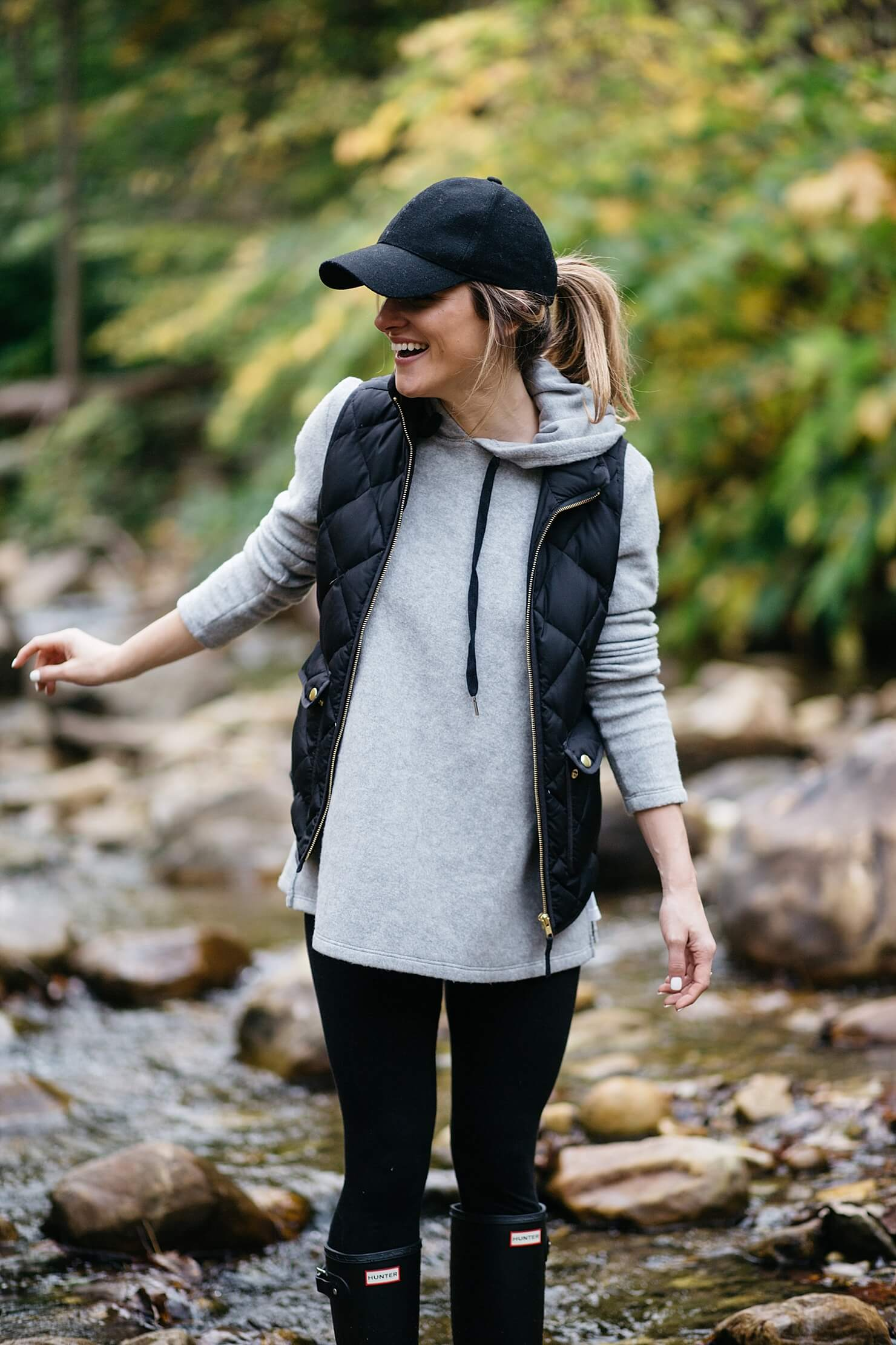 hunter boots outfit with a baseball cap and vest