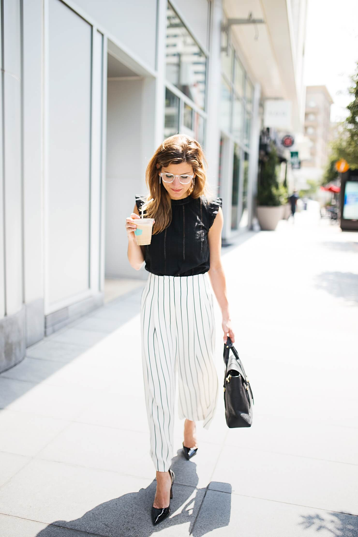 brighton keller wearing eyelet black top with striped culottes, wide leg pants and pumps